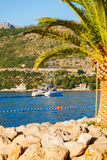 Boot im Meer nahe dem felsigen Ufer Dubrovnik, Kroatien Lizenzfreies Stockfoto