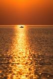 Boot im Sonnenuntergang im Meer mit Reflexionen und Wolken Lizenzfreie Stockbilder