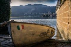 Boot klein met Italiaans vlagparkeren bij het strand stock afbeeldingen