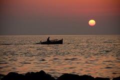 Boot in Meer auf Sonnenuntergang Lizenzfreie Stockfotos
