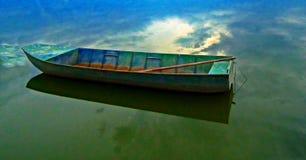 Boot met bezinning over het meer stock foto