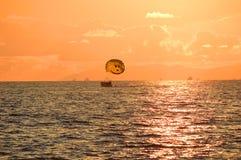 Boot met een valscherm bij zonsondergang Stock Foto's