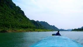 Boot met kapiteinsvlotters op rivier voorbij bosbouw heuvelige bank stock videobeelden