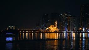 Boot met neonlichtvlotter door overzeese die lagune voor moskee met gouden licht wordt verlicht Nachtmening van grote stad stock videobeelden