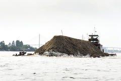 Boot mit dem Boden, der auf den Mekong mit Brücke Rach Mieu am 14. Februar 2012 in meinem Tho, Vietnam schwimmt Lizenzfreie Stockbilder