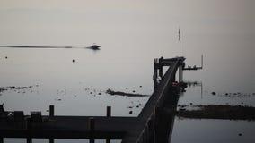Boot mit dem Wasserskifahrer, der durch einen Pier während des Sonnenaufgangs fährt stock video