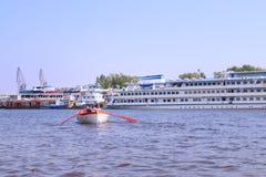 Boot mit den Rudern, die auf Fluss gegen Schiffe schwimmen lizenzfreies stockbild
