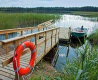 Boot mit einem hölzernen Pier auf dem See stockfotografie