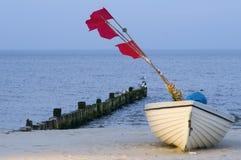 Boot mit roten Fahnen Stockbilder