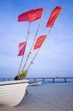 Boot mit roten flaggs auf einem Strand Lizenzfreie Stockfotografie