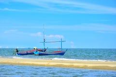 Boot mit zwei Fischern in einem Meer mit blauem Himmel in Thailand Stockfotografie