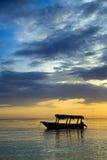 Boot nahe dem Strand bei Sonnenaufgang Stockbilder