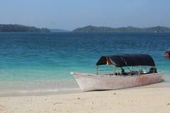 Boot onbeweeglijk bij een strand Stock Afbeelding
