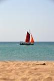 Boot onder rode zeilen in het overzees Stock Foto
