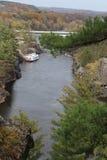 Boot op banken van rivier dichtbij weg Stock Afbeeldingen