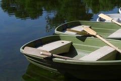 Boot op de kust van een meer met hun omhoog roeispanen wordt geparkeerd die Stock Afbeeldingen