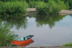 Boot op de kust van een rivier wordt geparkeerd die stock afbeeldingen