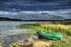 Boot op de kust van het meer vóór het onweer Stock Foto's