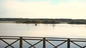 Boot op de roeispanen op de rivier bij zonsondergang stock videobeelden
