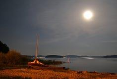 Boot op een meerkust bij nacht in het maanlicht Stock Afbeeldingen
