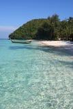 Boot op het duidelijke water, het strand en de bomen Stock Foto's