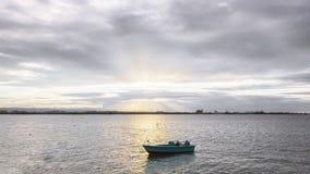 Boot op het Overzees tegen Zonsondergang en Bewolkte Hemel royalty-vrije stock afbeelding