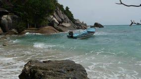 Boot op kust die dichtbij overzees golven Traditionele die boot op zandige kust dichtbij prachtige golvende overzees op zonnige d stock footage
