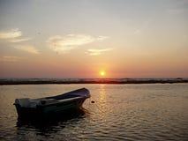 Boot op overzees bij zonsondergang Stock Afbeelding