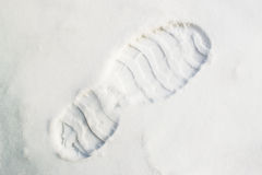 Boot Print in Snow. Single human bootprint in a diagonal composition in fresh crisp white snow royalty free stock image