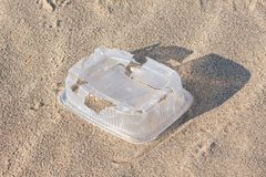 White plastic food container left by a man on the sand beach stock images
