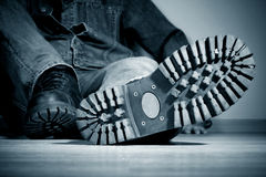 Boot protector. The young man sits on a floor. In the foreground a boot protector Royalty Free Stock Photos