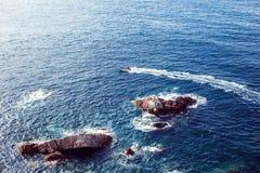Boot segelt nahe den Felsen im Wasser und hebt den Wasserweg auf Stockfoto