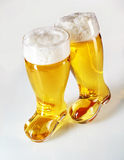 Boot shaped beer glasses filled with frothy lager Royalty Free Stock Photo