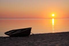 Boot silhoutte auf der Küste bei Sonnenuntergang Stockbilder
