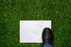 Boot standig on white sheet of paper on the grass Royalty Free Stock Photo