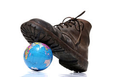 Boot stepping on planet. A worn boot is stepping on Planet Earth Stock Photos