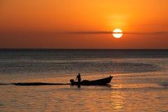 Boot tegen zonsondergang wordt gesilhouetteerd die Royalty-vrije Stock Afbeelding