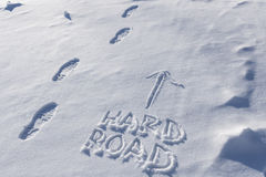 Boot Tracks On The Hard Road in Snow. Image showing boot imprints next to an arrow and the words hard road written in the snow royalty free stock image
