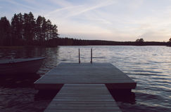 Boot und Anlegestelle durch See im schönen Sonnenuntergang Lizenzfreie Stockfotos
