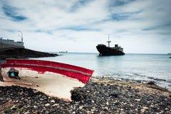 Boot und gebrochenes Schiff auf Lanzarote Stockfotografie