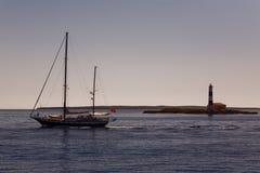 Boot und Leuchtturm am Sonnenuntergang Stockfoto