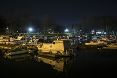 Boot und seine Reflexion im Wasser verankert im Hafen stockfotos