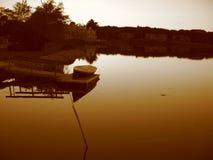 Boot und Teich am Sonnenuntergang im Sepia Stockbild