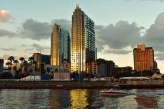 Boot und Wasserfahrzeug, die auf bunten Wolkenkratzern und Kunstmuseumhintergrund steuern stockfotografie