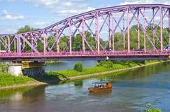 Boot unter der rosa Brücke stockbild