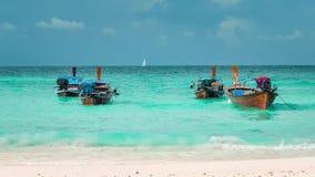 Boot vier met lange staart in blauwe golven op Bundhaya-strand slingeren, en witte zeilboot op de horizon, Koh Lipe Thailand die stock videobeelden