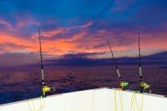 Boot visserij het met een sleeplijn vissen zonsondergang met staven en spoelen stock afbeeldingen