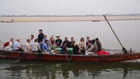 Boot voll von den Leuten, die durch Fluss der Ganges in Varanasi segeln stock footage