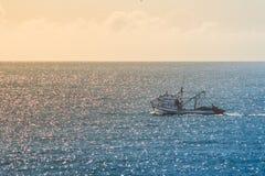 Boot, welches das Meer während eines schönen Sonnenuntergangs in FlorianÃ-³ polis, Santa Catarina, Brasilien kreuzt lizenzfreies stockbild