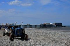 Boote, alter Traktor u. Cromer-Pier, Norfolk, Großbritannien Stockbild